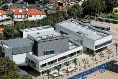 """<div style=""""text-align:center; color:white;""""><div style=""""font-size:17px; """">Fórum Machico</div><br>Cliente: Sociedade de Desenvolvimento de Porto Santo SA<br>Ano: 2001 – 2003</div>"""